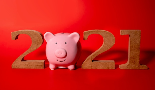 2021 houten karakter en roze spaarvarken op witte achtergrond, concept vakantie kerstmis nieuwjaar.