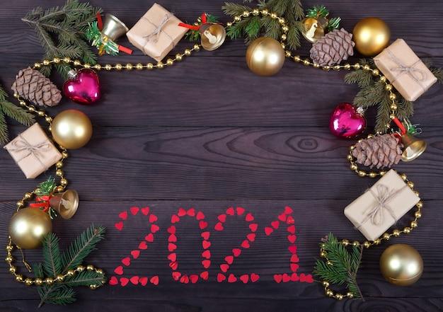 2021 inscriptie van harten, geschenken, sparren en sparren takken, ceder kegels en ballen op een deoevian bruin