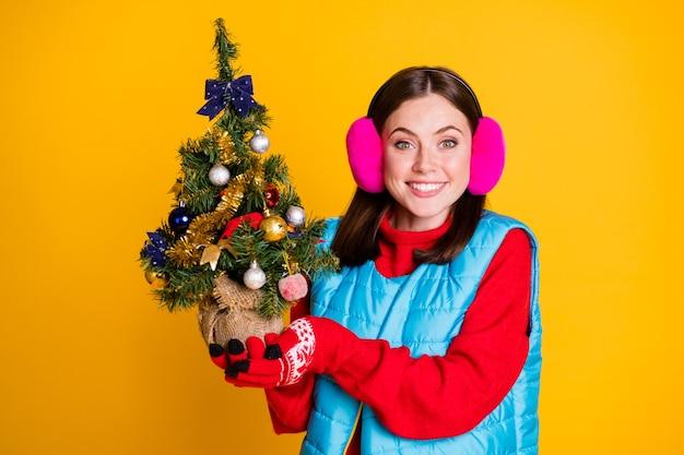 2021 kerstgeest vrolijk hulstvieringsconcept. positief meisje houdt groenblijvende dennen met klatergoud kerstballen speelgoed ornament draag roze trui geïsoleerd over heldere glans kleur achtergrond