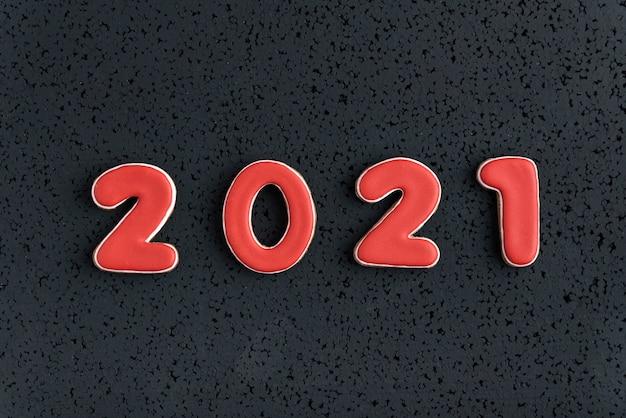 2021 nieuwjaar van peperkoek op zwarte achtergrond. bovenaanzicht van gemberbroodkoekjes.