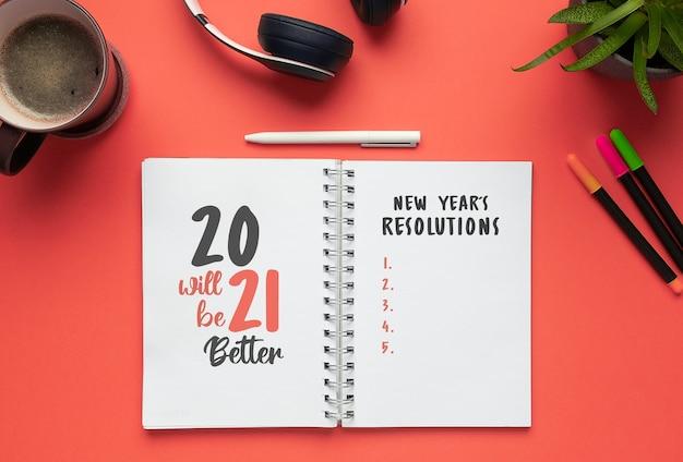 2021 nieuwjaarsnotitieboekje met lijst met resoluties op een rood