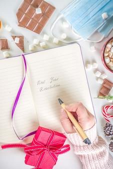 2021 pandemiejaar nieuwjaarsresolutieconcept. nieuwjaarsdoelen en resolutie achtergrond notitieblok met nieuwe normale covid levensdoelen, kerstdecor, warme chocolademelk