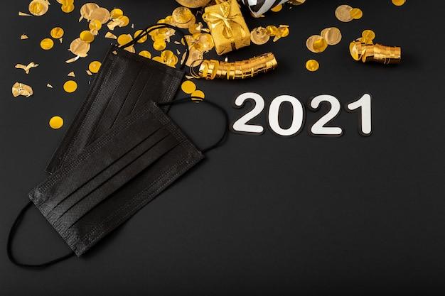 2021 tekst belettering met zwarte medische gezichtsmaskers, gouden kerstfeest decor. nieuwjaarscovid 19.