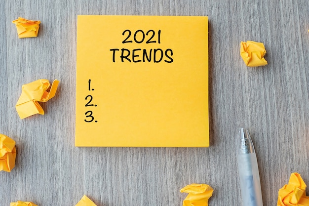2021 trends-woord op gele notitie met pen en verkruimeld papier