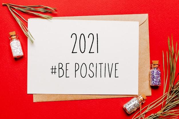 2021 wees een positieve kerstnoot met cadeau, dennentak en speelgoed op rood