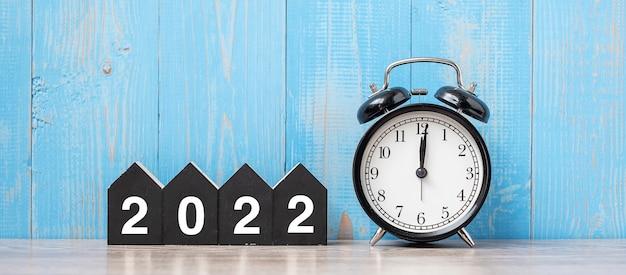 2022 gelukkig nieuwjaar met retro wekker en houten nummer. nieuwe start, resolutie, doelen, plan, actie en missieconcept