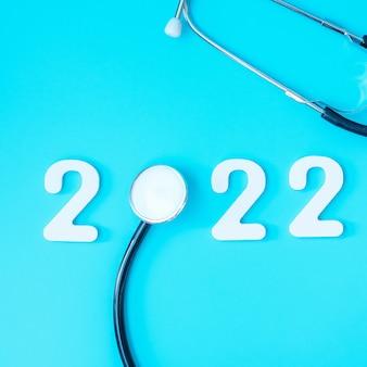 2022 gelukkig nieuwjaar voor gezondheidszorg, verzekeringen, wellness en medisch concept. stethoscoop en wit nummer op blauwe achtergrond