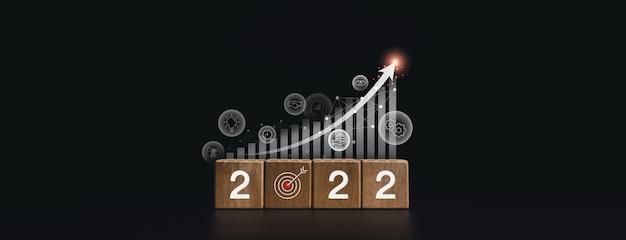 2022 gelukkig nieuwjaarbanner met doeldoel en succesvol concept. de 2022-nummers op houten kubusblokken met een groeimeter en bedrijfsstrategiepictogrammen op een donkere achtergrond, moderne en minimalistische stijl.