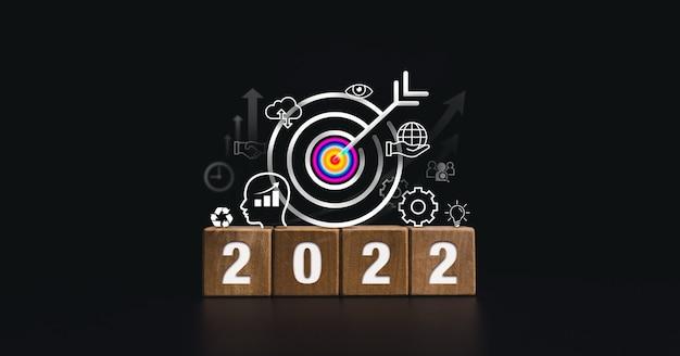 2022 gelukkig nieuwjaarbanner met groot doeldoel en succesvol concept. de 2022-nummers op houten kubusblokken met bedrijfsstrategiepictogrammen op een donkere achtergrond, moderne en minimalistische stijl.