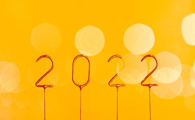 2022 gouden nummers op gele achtergrond met wazig bokeh licht gelukkig nieuwjaar en vrolijk kerstfeest