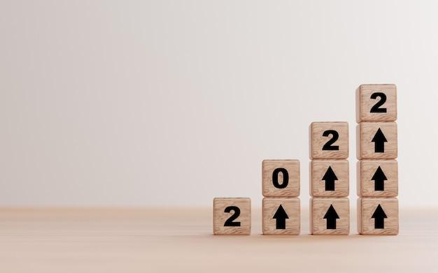 2022 jaar en pijl omhoog print scherm op houten kubusblok en kopieer ruimte voor voorbereiding start nieuw businessplan in 2022 door 3d render.