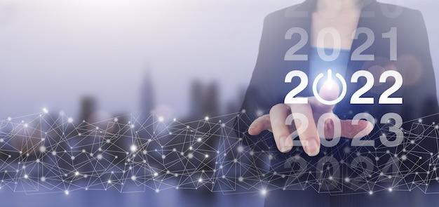 2022 nieuwe slimme technologie en nieuwe technologietrend in 2022. handaanraking digitaal scherm hologram 2022 teken op stadslicht wazige achtergrond. concept start nieuwjaar 2022