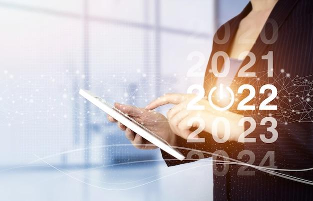 2022 nieuwjaar. nieuwjaarsconcept. handaanraking witte tablet met digitaal hologram 2022 teken op lichte onscherpe achtergrond. succes nieuwjaar concept. bedrijfsbeheer, ideeën voor inspiratieconcepten