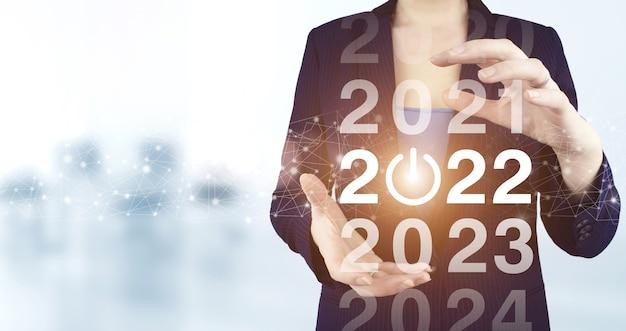 2022 nieuwjaar. twee handen met virtueel holografisch 2022-pictogram met lichte onscherpe achtergrond. gelukkig nieuwjaar 2022. succes nieuwjaar concept. bedrijfsbeheer, inspiratie concepten ideeën.