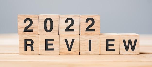 2022 review kubusblok op tafelachtergrond. resolutie, plan, verandering, start en nieuwjaarsvakantieconcepten