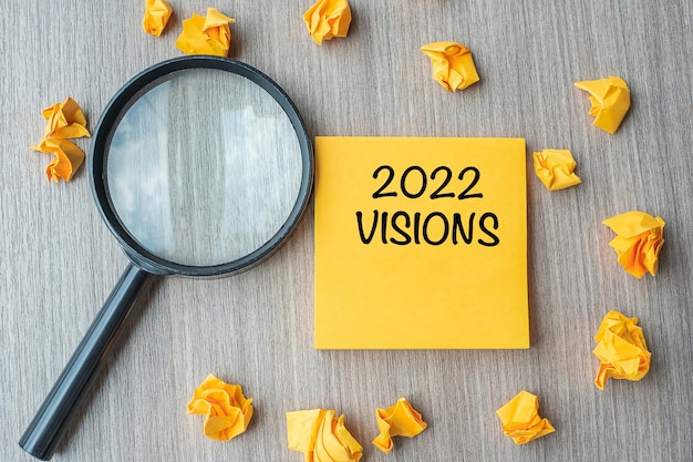 2022 visies woorden met verkruimeld papier en vergrootglas