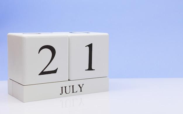 21 juli. dag 21 van de maand, dagelijkse kalender op witte tafel met reflectie, met lichtblauwe achtergrond.