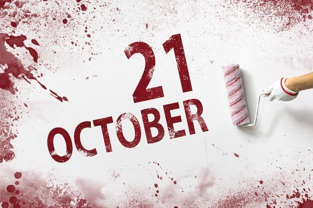 21 oktober. dag 21 van de maand, kalenderdatum. de hand houdt een roller met rode verf vast en schrijft een kalenderdatum op een witte achtergrond. herfstmaand, dag van het jaarconcept.