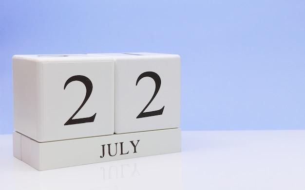22 juli. dag 22 van de maand, dagelijkse kalender op witte tafel met reflectie, met lichtblauwe achtergrond.