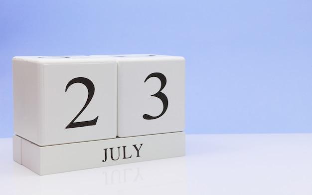 23 juli. dag 23 van de maand, dagelijkse kalender op witte tafel met reflectie, met lichtblauwe achtergrond.