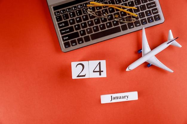 24 januari-kalender met accessoires op zakelijke werkruimte bureau op computertoetsenbord, vliegtuig, glazen rode achtergrond