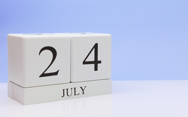 24 juli. dag 24 van de maand, dagelijkse kalender op witte tafel met reflectie, met lichtblauwe achtergrond.