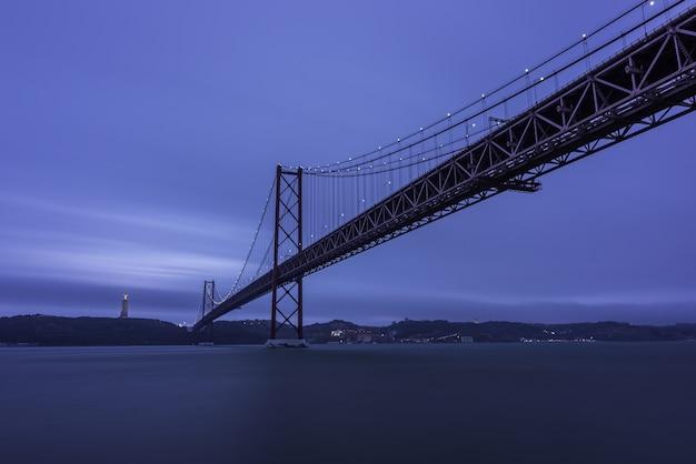 25 de abril brug over de taag, omgeven door heuvels en 's avonds lichten