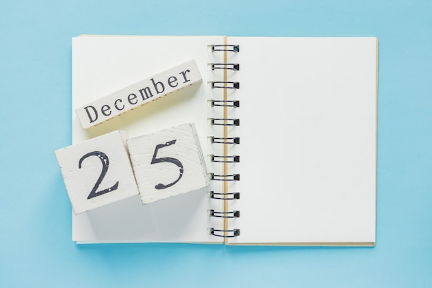 25 december op een houten kalender op een leerboek. kerstmis en nieuwjaarconcept