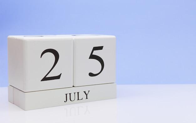 25 juli. dag 25 van de maand, dagelijkse kalender op witte tafel met reflectie, met lichtblauwe achtergrond.
