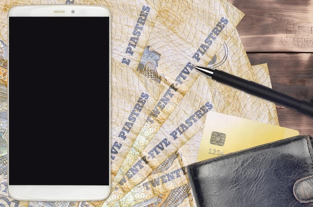 25 rekeningen egyptische piasters en smartphone met portemonnee en creditcard. e-betalingen of e-commerce concept. online winkelen en zakendoen met gebruik van draagbare apparaten