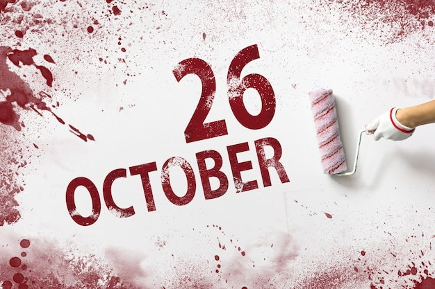 26 oktober. dag 26 van de maand, kalenderdatum. de hand houdt een roller met rode verf vast en schrijft een kalenderdatum op een witte achtergrond. herfstmaand, dag van het jaarconcept.