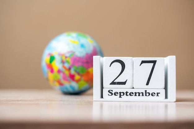 27 september van kalender houten op tafel, woord toerisme dag concept