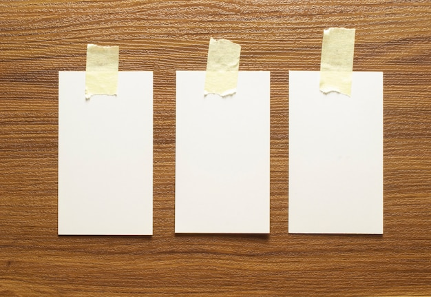3 blanco visitekaartjes gelijmd met gele tape op een houten oppervlak, 3,5 x 2 inch formaat