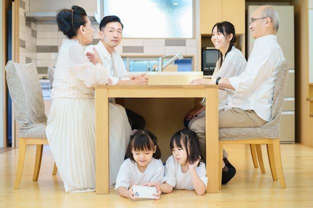 3 generaties familiebijeenkomst aan tafel in de kamer