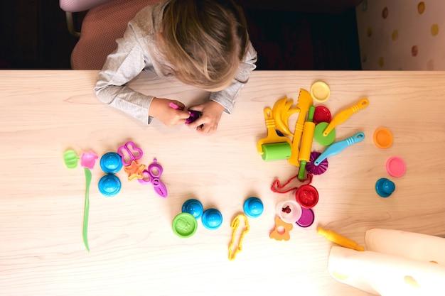 3 jaar meisje creatieve kunsten. kindhanden die met kleurrijke kleiplasticine spelen. zelfisolatie covid-19, online onderwijs, thuisonderwijs. peutermeisje dat thuis studeert, thuis leert