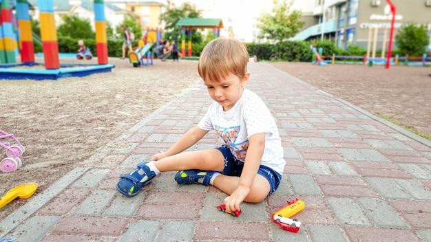 3 jaar oud jongetje in t-shirt en korte broek zittend op de grond in de speeltuin en spelend met veel kleurrijk speelgoed