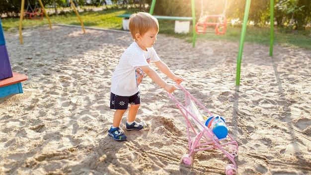 3 jaar oud jongetje met speelgoedkinderwagen voor poppen die op de speelplaats in het park spelen