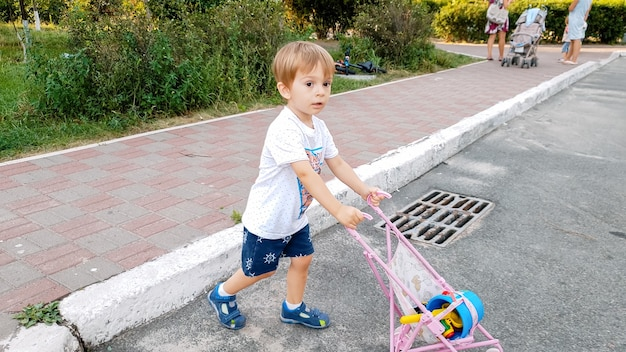 3 jaar oude peuterjongen die met speelgoedkinderwagen op straat loopt. jongen spelen met speelgoed voor meisjes.