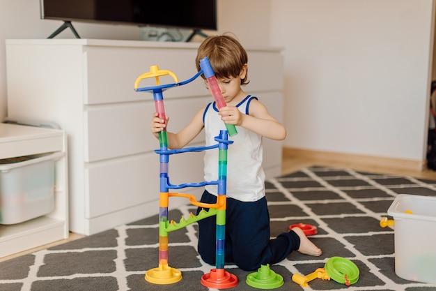 3-jarige jongen bouwt plastic constructie zittend op de vloer van het huis. concept van eenzaamheid en kinderen met autismeproblemen.