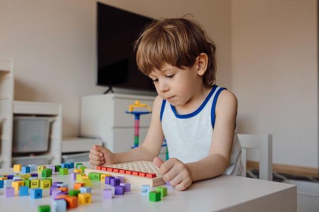 3-jarige jongen wordt ondergedompeld in zijn eigen wereld. kinderobsessie met getallen en tellen. manifestatie van autisme bij kinderen.