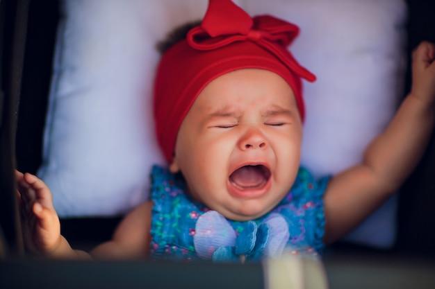3 maanden oude baby in rolstoel op straat huilt