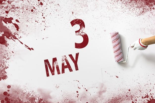 3 mei. dag 3 van de maand, kalenderdatum. de hand houdt een roller met rode verf vast en schrijft een kalenderdatum op een witte achtergrond. lente maand, dag van het jaar concept. Premium Foto
