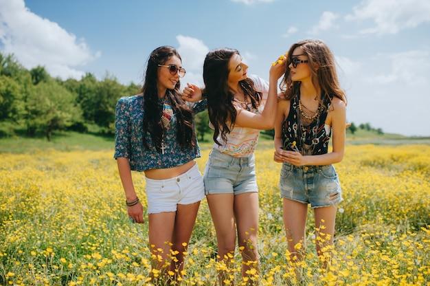 3 mooi hippiemeisje op een gebied van gele bloemen
