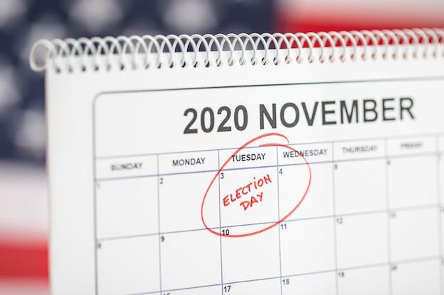 3 november 2020 concept verkiezingsdag. bureaukalender met 3 november gemarkeerd in het rood en de vlag van de vs op de achtergrond