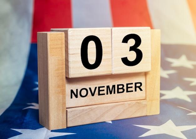 3 november, verkiezingsdag in de vs. datum op houten kalender met amerikaanse vlag op achtergrond.
