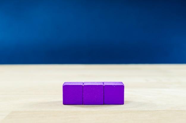 3 paarse houten blokken in een rij geplaatst op een massief eiken tafel, met kopie ruimte, over blauwe achtergrond.