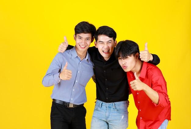 3 volwassenen aziatische knappe en slimme mannen glimlachen en duimvingers omhoog kijken, voelen geluk, kijken naar de camera. schieten in studio met geïsoleerde gele achtergrond. in concept geluk en succesvol.