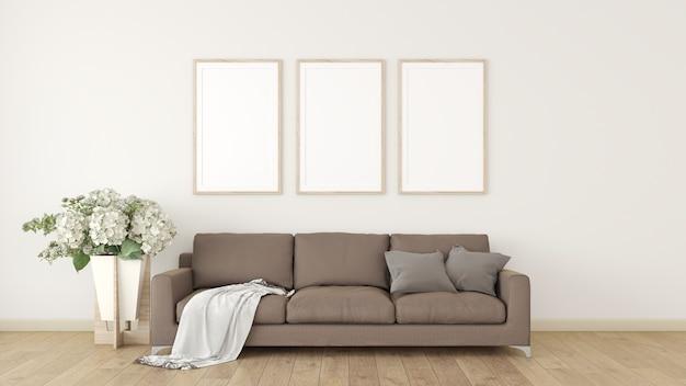 3 witte fotolijsten op de crème wand het interieur is versierd met bruine banken, kussens en plantenpotten op de houten vloer.