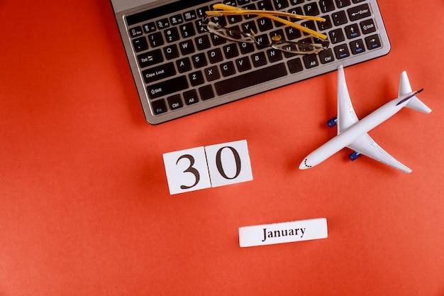 30 januari-kalender met accessoires op zakelijke werkruimte bureau op computertoetsenbord, vliegtuig, glazen rode achtergrond
