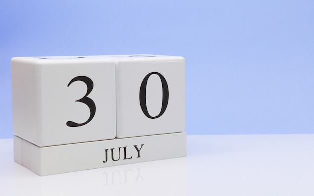 30 juli. dag 30 van de maand, dagelijkse kalender op witte tafel met reflectie, met lichtblauwe achtergrond.